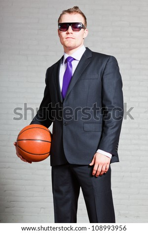 Business man with basketball. Wearing dark sunglasses. Good looking young man with short blond hair. White brick wall. - stock photo