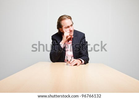 Business man with blond hair sitting bored behind table in boardroom isolated on white background - stock photo