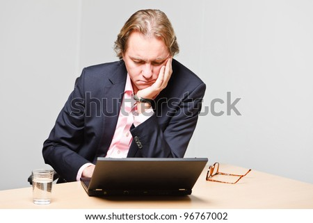Business man with blond hair working with laptop computer sitting behind desk in office isolated on white background. Wearing pink shirt and blue suit. - stock photo