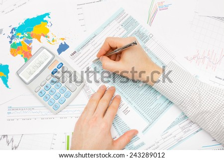 Business man with calculator and financial charts and graphs - stock photo