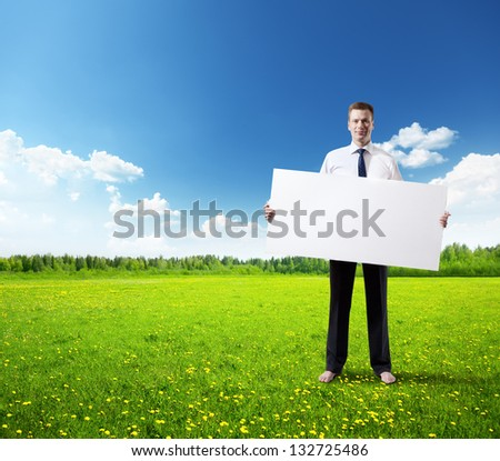 business man with empty board in hand on field of spring grass - stock photo