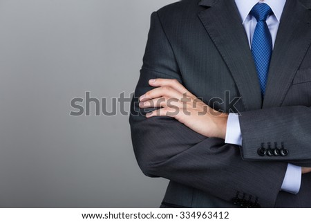 Business man with folded hands against gray background. Copy space - stock photo