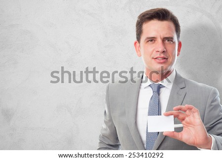 Business man with grey suit. He is holding a white card. Over concrete wallpaper - stock photo