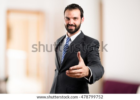 Business man with his arms crossed on unfocused background