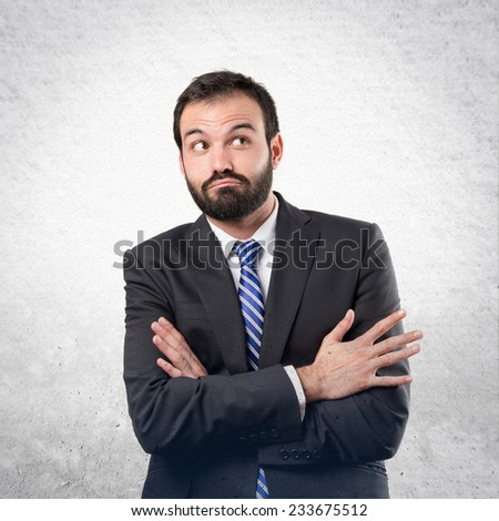 Business man with his arms crossed over textured background  - stock photo