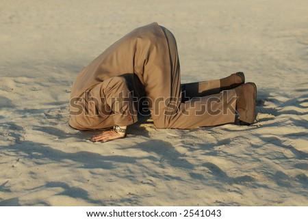 business man with his head buried in the sand - stock photo
