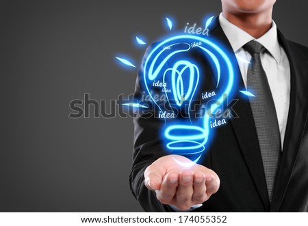 Business man with idea light bulb on virtual background - stock photo