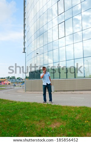 Business man with metal case and mobile phone in front of modern business building.