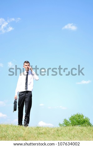 Business man with phone in nature - stock photo