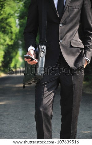 Business man with phone on road - stock photo