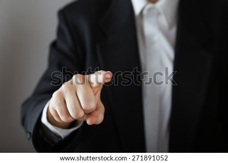 Business man with pointing to something or touching a touch screen on grey background - stock photo