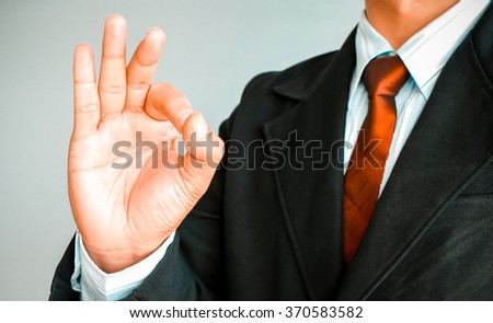 Business man with red tie in suit showing OK sign on gray background, Successful concept. - stock photo