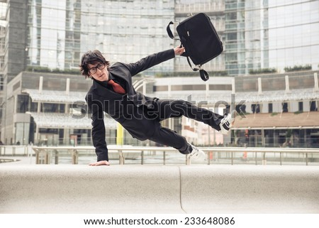 Business man with suitcase jumping over urban obstacles - Man with elegant suit running at work because in late - Concepts of business,overcoming problems,competition and urban urban life  - stock photo