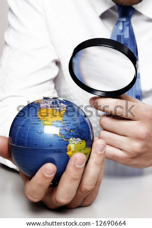 Business man with the earth under a magnifying glass - stock photo
