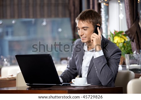 Business man with the laptop uses a mobile communication in cafe - stock photo