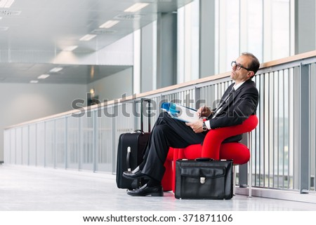 Business man with trolley and suitcase reading business catalog on red armchair at exhibition lobby