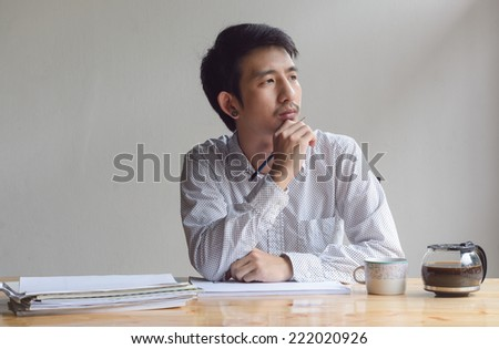 business man working and think with paper sheet at work table