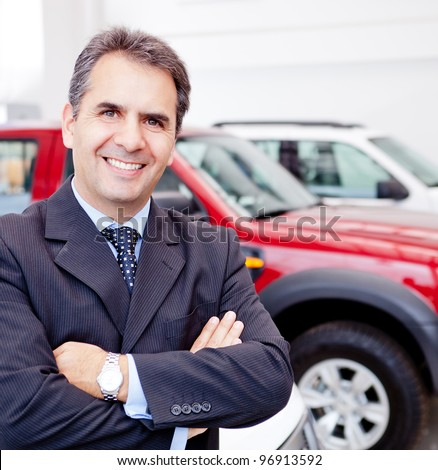 Business man working at a car dealer smiling - stock photo