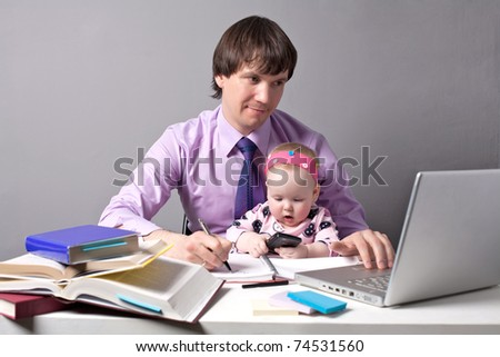 Business man working in the office with his daughter - stock photo