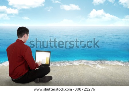 Business man working on the beach with blue sky background - stock photo