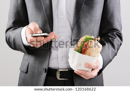 Business man working on the go with smart phone and take away sandwich lunch - stock photo
