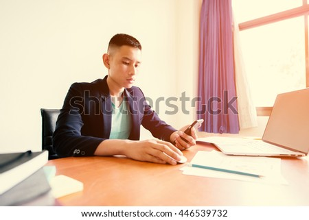 business man working using smartphone and notebook computer on wooden table in office