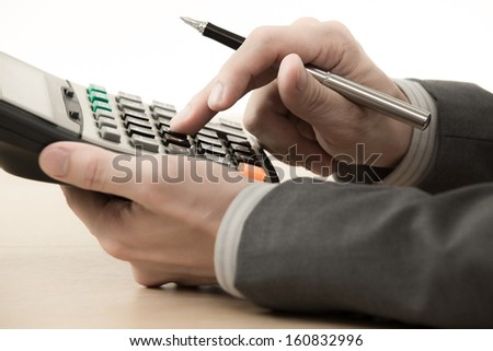 Business man working with calculator on table - stock photo