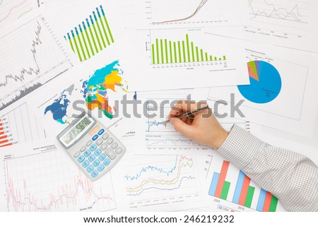 Business man working with financial data - pen in hand - stock photo