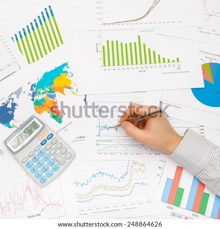 Business man working with financial data - pen in hand - studio shot - stock photo