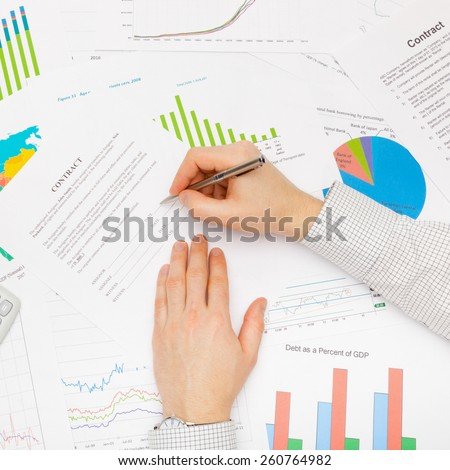 Business man working with financial data - preparing for signing contract - studio shot - stock photo