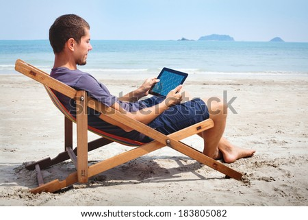 business man working with tablet on the beach - stock photo