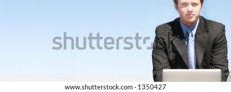Business Man works on his laptop outside in the blue sky - stock photo