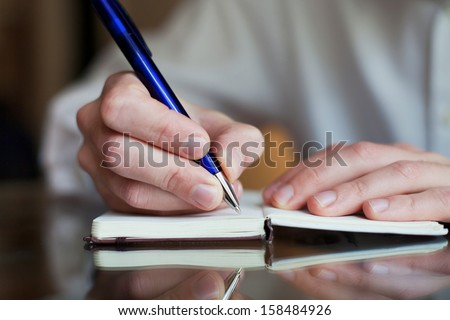business man write in the notepad - stock photo