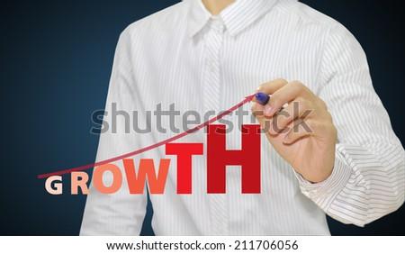 Business man writing a growing graph  - stock photo