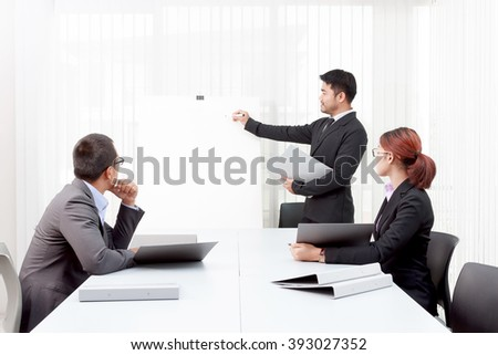 Business man writing for explaining something to colleagues at conference table - stock photo