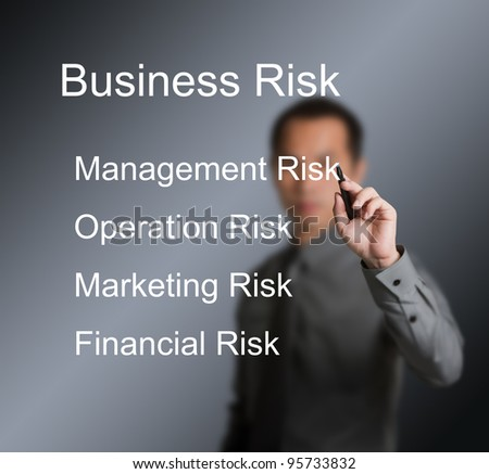 business man writing four type of business risk ( management - operation - marketing - financial ) on whiteboard