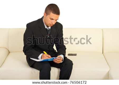 Business man writing in a folder and sitting on sofa in office