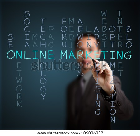 business man writing online marketing  concept by crossword of relate word such as internet, technology, advertising, seo, website, media, etc. - stock photo