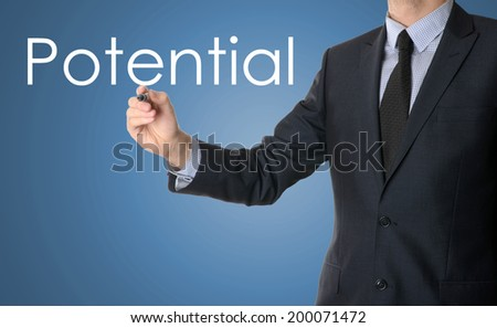 business man writing potential on blue background - stock photo