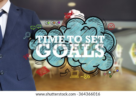 business man writing TIME TO SET GOALS over the cloud with office background , business concept , business idea - stock photo