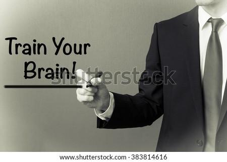 Business man writing - Train Your Brain! - stock photo