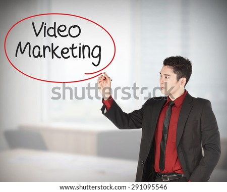 Business man writing video marketing with handwriting and circle