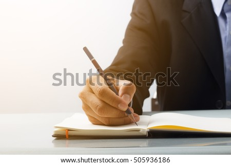 Business man writing with blue pencil at the desk