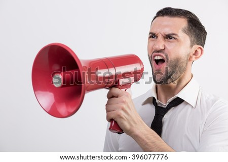 Business man yells into a red loudspeaker against white background