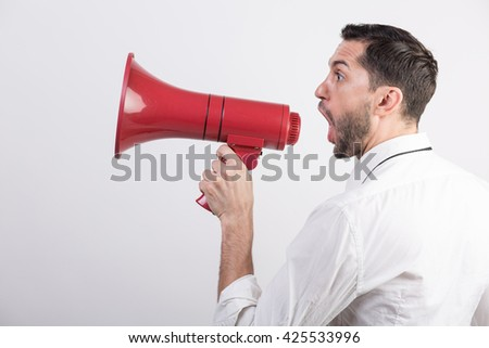 Business man yells into a red loudspeaker against white background - stock photo