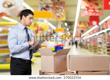 Business. Manager In Warehouse Checking Boxes Using Digital Tablet - stock photo