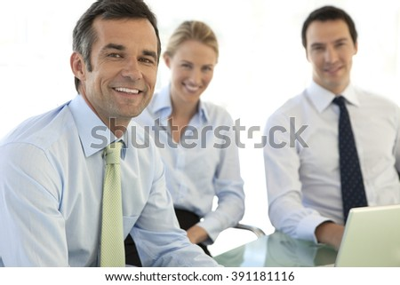 Business managers meeting and working on same laptop together - stock photo