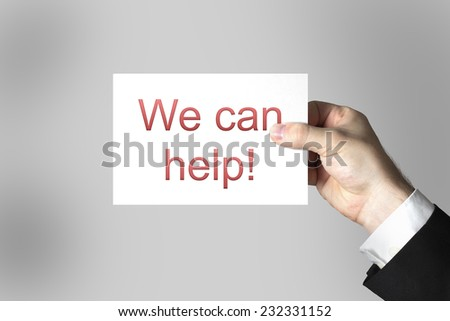 business mans hand holding card sign we can help - stock photo