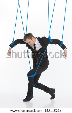 Business marionette. Young man in formalwear looking like marionette moving against white background - stock photo