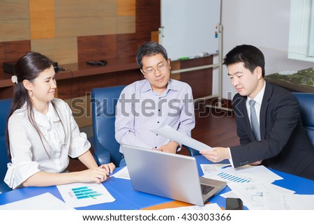 Business meeting, Asian people sitting for a table with business plan on high floor in the office. Asian nationality male in suit shows a business graph of his business partner.  - stock photo